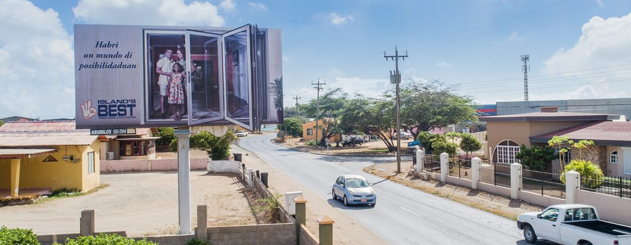 A bigger then life sized billboard next to a busy road with an advertisement for Island's Best